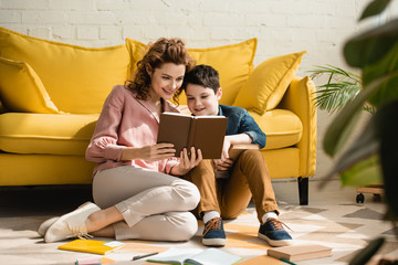 smiling mother and son sitting on floor near yellow sofa and reading book together
