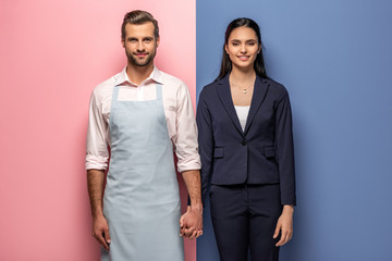 smiling man in apron and businesswoman holding hands on blue and pink - fototapety na wymiar