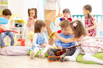 Group of kids playing with musical instruments in daycare