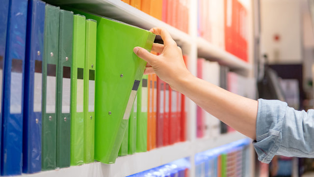 Male hand choosing new green ring binder file folder from colorful shelf display in stationery shop. Buying office supplies concept