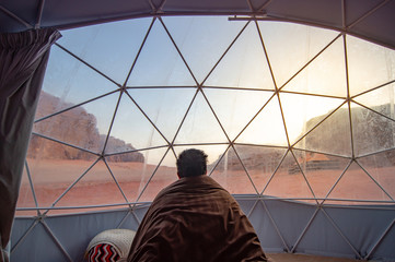 Tourist man staying in blanket in dome tent looking outside at Wadi Rum desert, famous natural attraction in Jordan. Travel Middle east concept