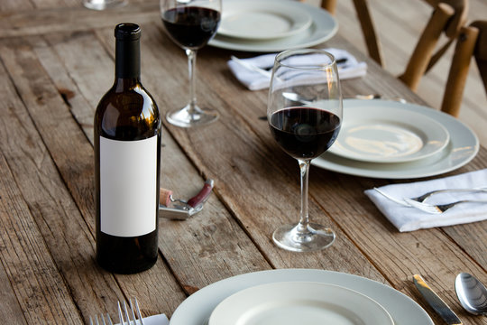 bottle of red wine and two glasses on wooden table