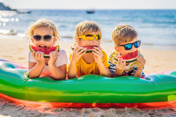 Children eat watermelon on the beach in sunglasses