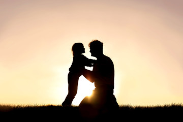 Silhouette of Happy Father and his Little Child Smiling and Playing at Sunset Wall mural