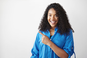 Big sale. Picture of stylish cheerful young mixed race woman with voluminous hair sharing useful information with you, pointing fore finger at white copyspace studio wall and smiling joyfully