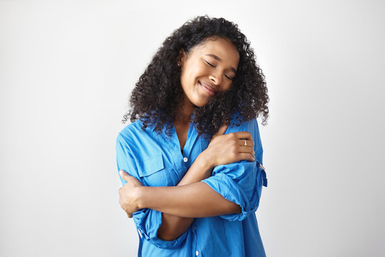 Picture of gorgeous pleased happy young Afro American woman with curly hair posing in studio with eyes closed and keeping arms around her shoulders, expressing love to herself. Body language