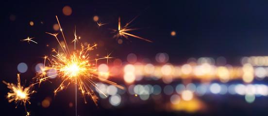 Glittering burning sparkler against blurred bokeh light background Wall mural