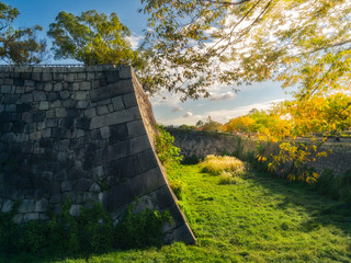 Early morning sun at the moat and fortifications of Osaka Castle in Japan, with people at the Otemon Gate in the background.