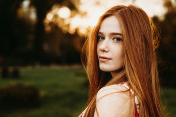 Portrait of a beautiful redhead woman with green eyes and freckles looking at camera against sunset outside over the shoulder.