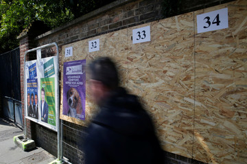 A man walks past official European election posters in a street in Amiens