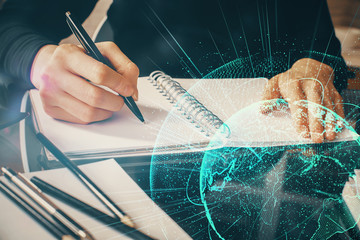 Social network theme hologram over hands taking notes background. Concept of global international people connect. Double exposure