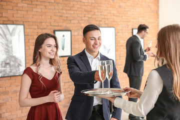 Waiter suggesting champagne to visitors of modern art gallery
