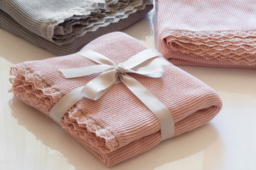 The pink plaid trimmed with lace is lying . The plaid  is folded and crossed a ribbon. Two more plaid lie next to them pink and gray. The gift is ready.