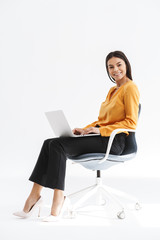 Portrait of attractive young businesswoman sitting in chair and using laptop while working in bright office