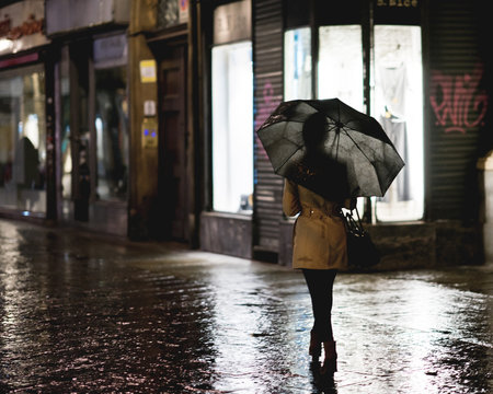 Walking in the city street under the rain with umbrella