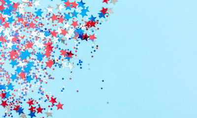 4th of July American Independence Day. Red, blue and white star confetti decorations on blue background. Flat lay, top view, copy space