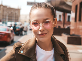 Portrait of beautiful brunette model dressed in summer hipster jacket clothes. Trendy girl posing in the street background. Funny and positive woman in round sunglasses