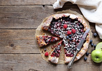 Galette with apples and fresh seasonal berries. Flat lay of crunchy summer berry tart  on rustic wooden table.