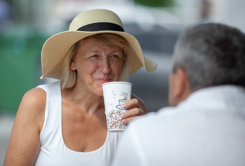 Mature couple having a coffee break. Focus on cheerful woman in summer hat with coffee cup