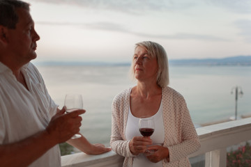 Senior couple having a romantic evening. Man and woman with wine looking at each other. View at the balcony against the sea