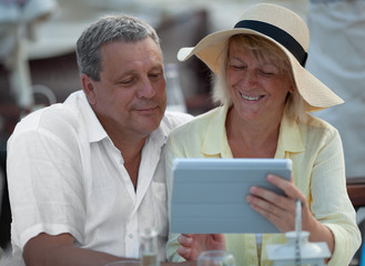 Happy mature couple with digital tablet watching photos or surfing the net together
