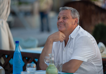 Mature man with kind smile and romantic look in outdoor cafe