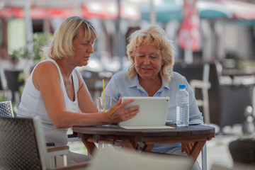 Two senior women friends having drinks in outdoor cafe and using tablet computer