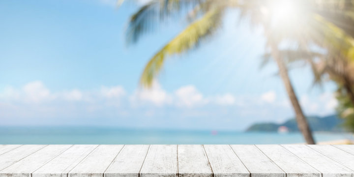 Empty wood table top and blurred summer beach with blue sea and sky banner background. - can used for display or montage your products.
