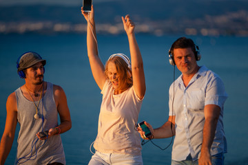 Group of three young people feeling free, enjoying life and excited with music. Woman and two men with mobiles and headphones outdoor