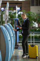 Woman traveler with ID using check-in terminal at the airport. Self-service kiosks