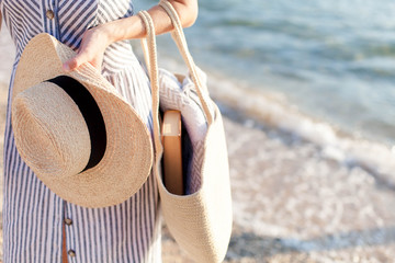 Woman at sea beach. Girl holds straw hat and bag with book and plaid. Traveler is enjoying summer vacation and holidays.
