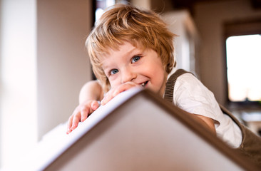 A toddler boy playing with a carton paper house indoors at home.