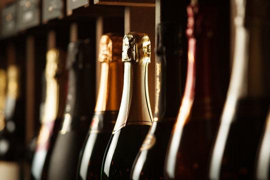 Underground cellar with elite sparkling wine on shelves, close up horizontal photo.
