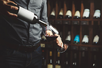 Fototapeta Close up shot of sommelier pouring red wine from bottle in glass on underground cellar background