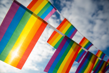 Gay pride rainbow flag bunting fluttering in the sky backlit by golden sun