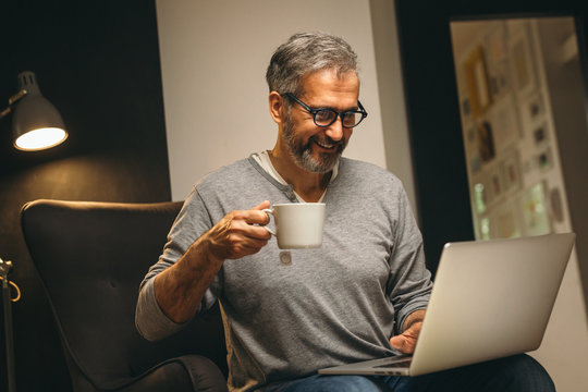 middle aged man using laptop and drinking tea relaxed in his sofa at home