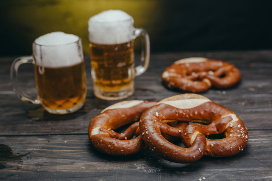 pretzels and beer in mug on dark wooden table