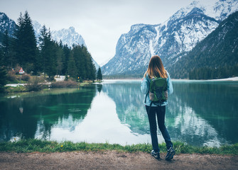 Young woman with backpack is standing on the coast of mountain lake at cloudy day in spring. Travel in Italy. Landscape with slim girl, reflection in water, snowy rocks, green trees. Vintage toning