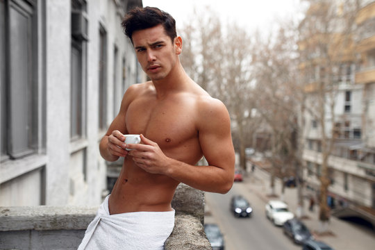 Brunette young man on balcony drink a cup of coffee outside, shirtless, sexy toned body. Fresh morning break.