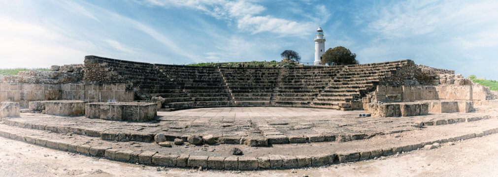 Ancient Odeon amphitheatre in Paphos Archaeological Park (Kato Pafos), harbour of Paphos, Cyprus, panoramic view. Scenic landscape with ruin of medieval architecture, lighthouse and sky, vintage image