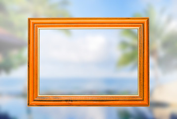Empty woodden vintage frame with blurry blackground  swimming pool and the blue sea with palm,coconut trees with background white clouds and blue sky,  peacful and realax,