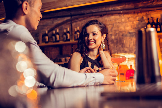 Girlfriend smiling while spending time with her man in bar