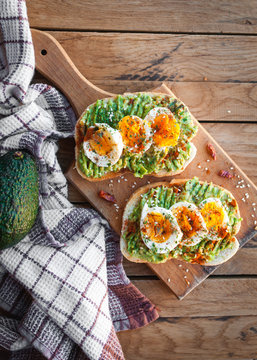 Avocado and egg toast with herbs and seasonings, on cutting board, top view