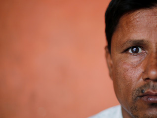 Sharfuddin, a cloth shop owner, poses for a picture inside his house in Nayabans