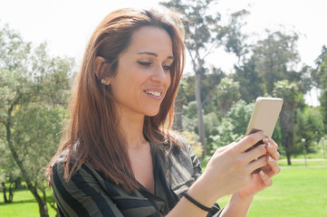 Positive satisfied lady chatting on smartphone outdoors. Young woman standing in park, using mobile phone and smiling at screen. Connection outdoors concept