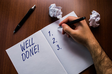 Text sign showing Well Done. Business photo text used praising demonstrating or group for something have done good way Upper close up view open notebook man hand pen paper balls wooden table