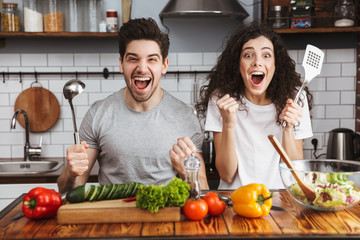 Excited cheerful young couple cooking healthy salad
