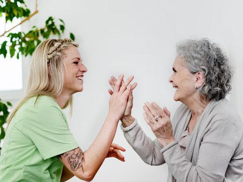 Seniorin und Pflegerin haben Spass