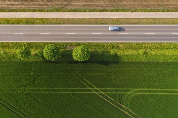 Aerial view of two lane road through countryside and cultivated fields with cars. Drone shot and copy space for text