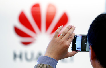 A man takes a picture of a Huawei logo at the Huawei European Cybersecurity Center in Brussels